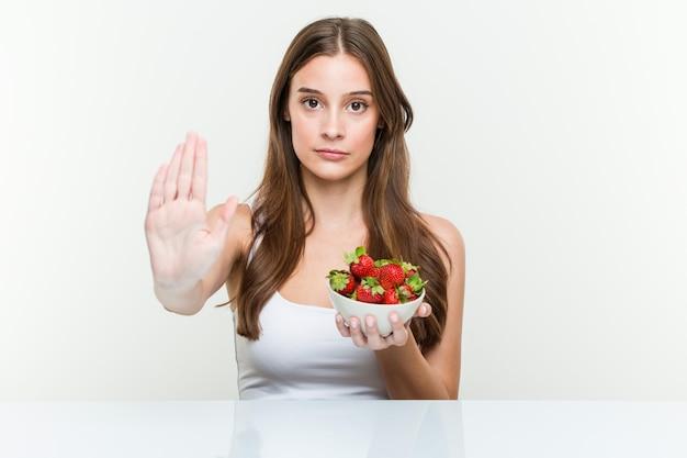 Jeune femme caucasienne tenant un bol de fraises debout avec la main tendue montrant le panneau d'arrêt, vous empêchant.