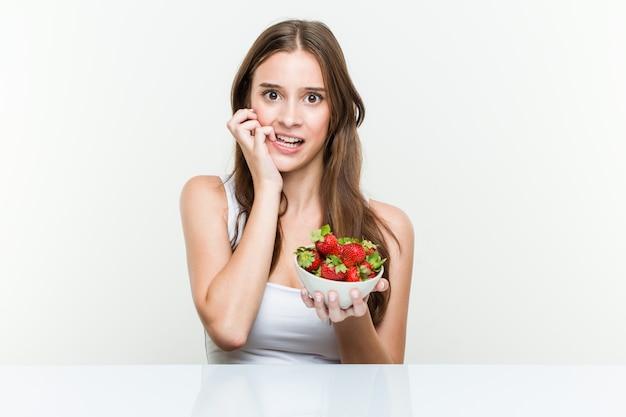 Jeune femme caucasienne tenant un bol de fraises se ronger les ongles, nerveuse et très inquiète.