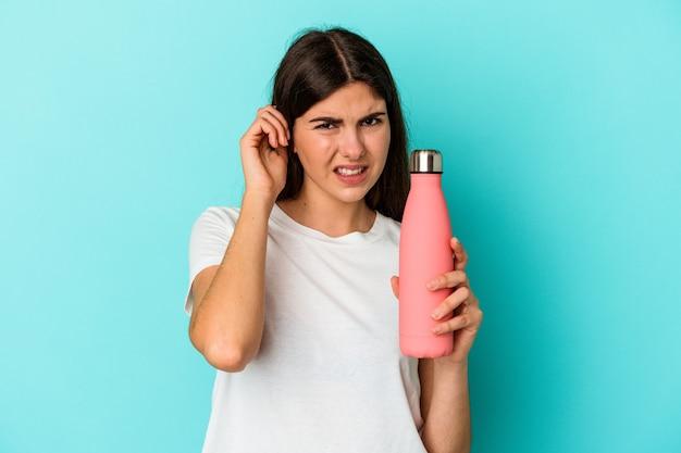 Jeune femme caucasienne tenant une bouteille d'eau isolée sur un mur bleu couvrant les oreilles avec les mains.