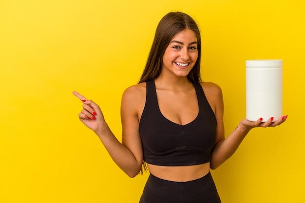 Jeune femme caucasienne tenant une bouteille de protéines isolée sur fond jaune souriant et pointant de côté, montrant quelque chose dans un espace vide.