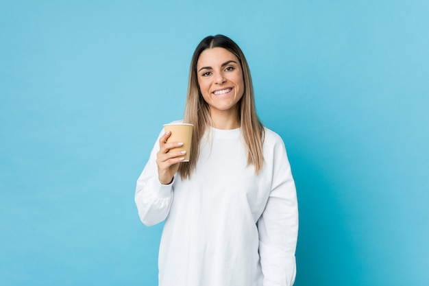 Jeune femme caucasienne tenant un café à emporter heureux, souriant et gai.