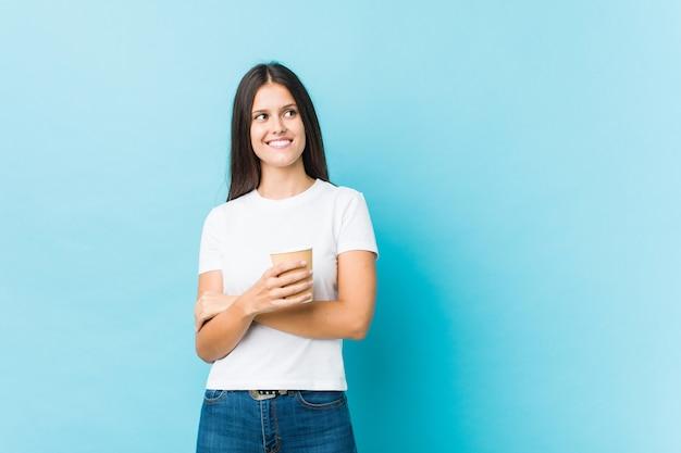 Jeune femme caucasienne tenant un café à emporter souriant confiant avec les bras croisés.