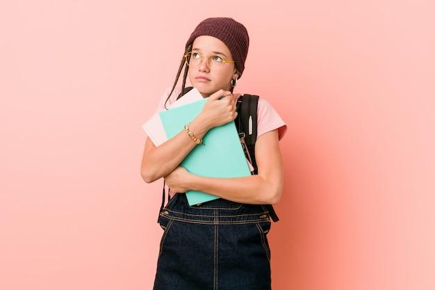 Jeune femme caucasienne tenant des cahiers à la recherche sur le côté avec une expression douteuse et sceptique.