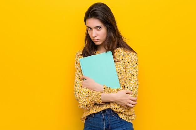 Jeune femme caucasienne tenant des cahiers