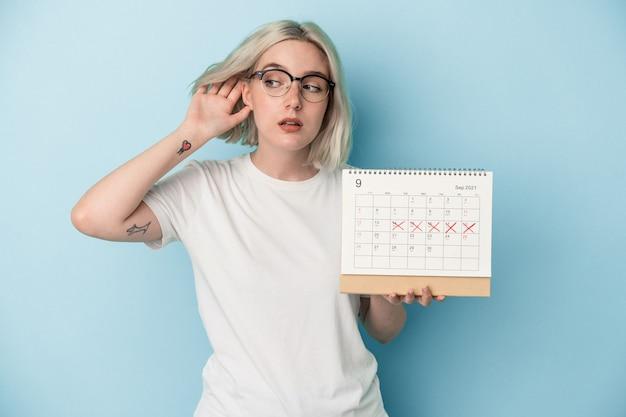 Jeune femme caucasienne tenant un calendrier isolé sur fond bleu essayant d'écouter un potin.