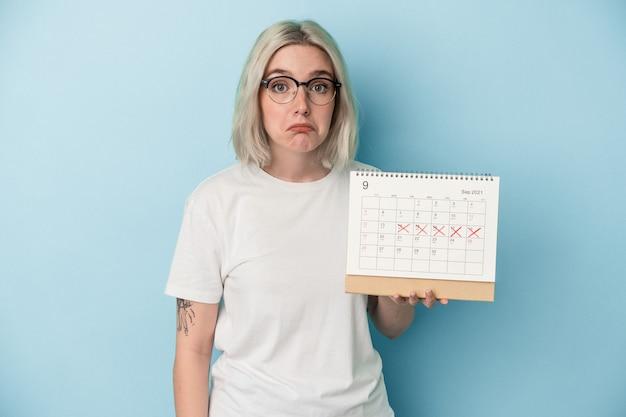 Jeune femme caucasienne tenant un calendrier isolé sur fond bleu hausse les épaules et ouvre les yeux confus.
