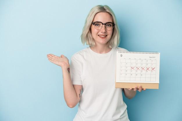 Jeune femme caucasienne tenant un calendrier isolé sur fond bleu montrant un espace de copie sur une paume et tenant une autre main sur la taille.
