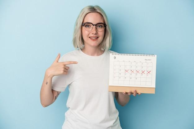 Jeune femme caucasienne tenant un calendrier isolé sur fond bleu personne pointant à la main vers un espace de copie de chemise, fière et confiante