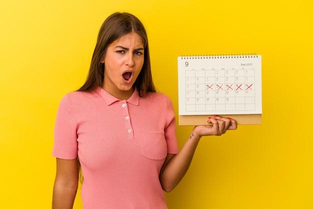 Jeune femme caucasienne tenant un calendrier isolé sur fond jaune criant très en colère et agressive.