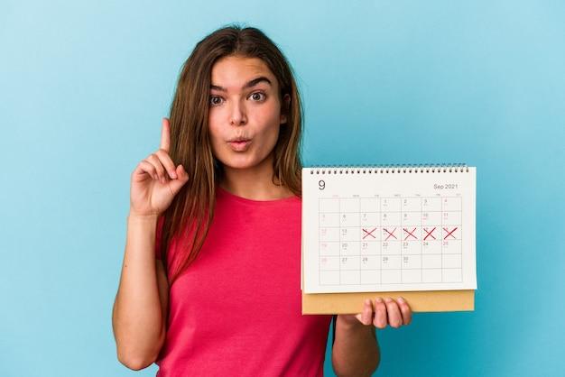 Jeune femme caucasienne tenant un calendrier isolé sur fond rose ayant une bonne idée, concept de créativité.