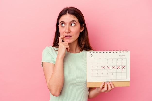 Jeune femme caucasienne tenant un calendrier isolé sur fond rose détendue en pensant à quelque chose en regardant un espace de copie.