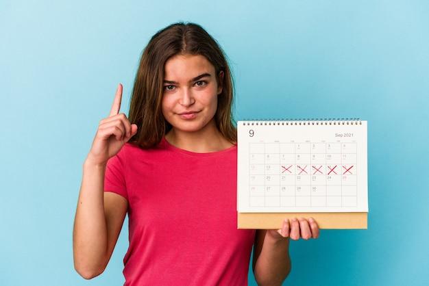 Jeune femme caucasienne tenant un calendrier isolé sur fond rose montrant le numéro un avec le doigt.