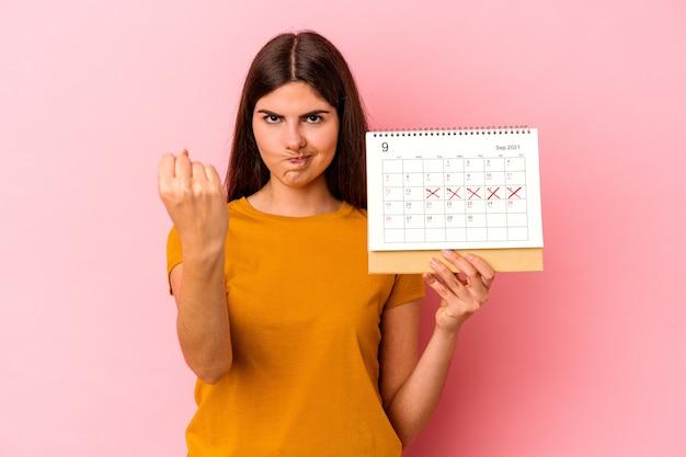 Jeune femme caucasienne tenant un calendrier isolé sur fond rose montrant le poing à la caméra, expression faciale agressive.