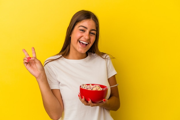 Jeune femme caucasienne tenant des céréales isolées sur fond jaune joyeuse et insouciante montrant un symbole de paix avec les doigts.