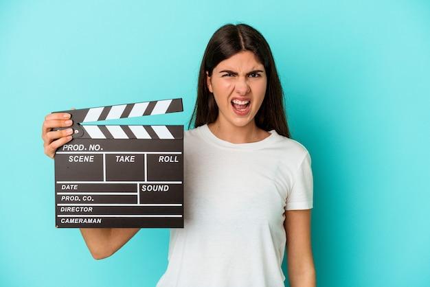 Jeune femme caucasienne tenant un clap isolé sur fond bleu criant très en colère et agressif.