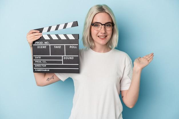 Jeune femme caucasienne tenant un clap isolé sur fond bleu montrant un espace de copie sur une paume et tenant une autre main sur la taille.