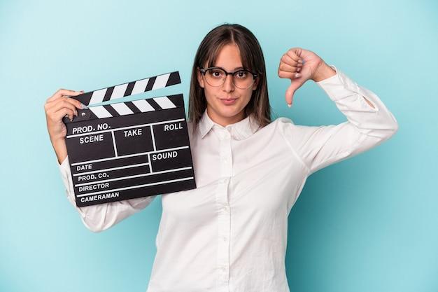 Jeune femme caucasienne tenant un clap isolé sur fond bleu montrant un geste d'aversion, les pouces vers le bas. notion de désaccord.
