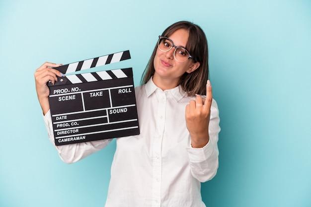 Jeune femme caucasienne tenant un clap isolé sur fond bleu pointant du doigt vers vous comme si vous vous invitiez à vous rapprocher.
