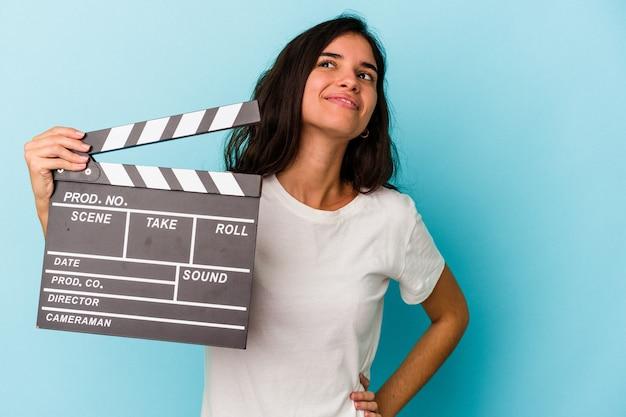 Jeune femme caucasienne tenant un clap isolé sur fond bleu rêvant d'atteindre des objectifs et des buts