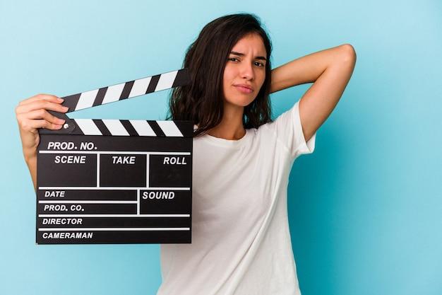 Jeune femme caucasienne tenant un clap isolé sur fond bleu touchant l'arrière de la tête, pensant et faisant un choix.