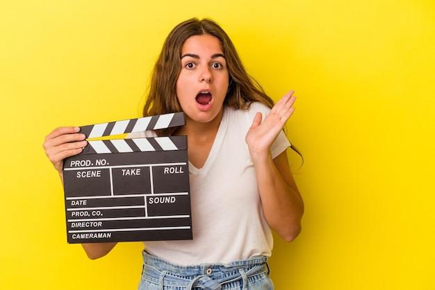 Jeune femme caucasienne tenant un clap isolé sur fond jaune surpris et choqué.
