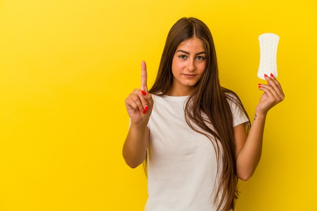 Jeune femme caucasienne tenant une compresse isolée sur fond jaune montrant le numéro un avec le doigt.
