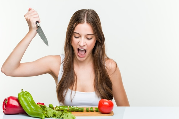 Jeune femme caucasienne tenant un couteau et couper des légumes