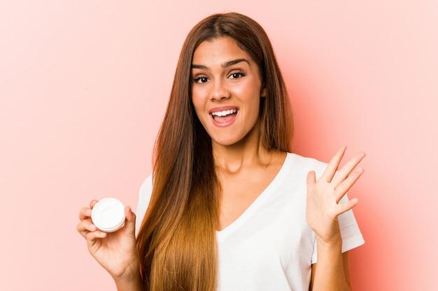 Jeune femme caucasienne tenant une crème hydratante célébrant une victoire ou un succès