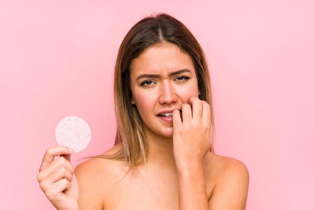 Jeune femme caucasienne tenant un disque facial isolé des ongles mordants, nerveux et très anxieux.