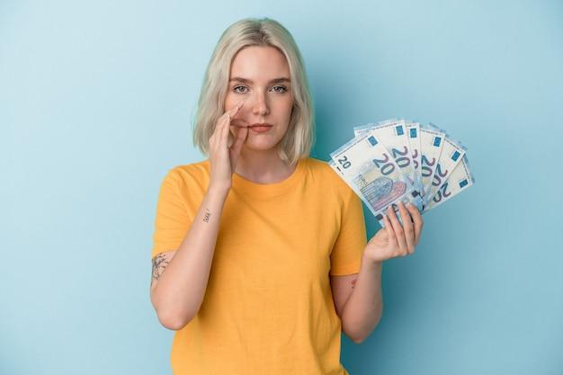 Jeune femme caucasienne tenant des factures isolées sur fond bleu avec les doigts sur les lèvres gardant un secret.