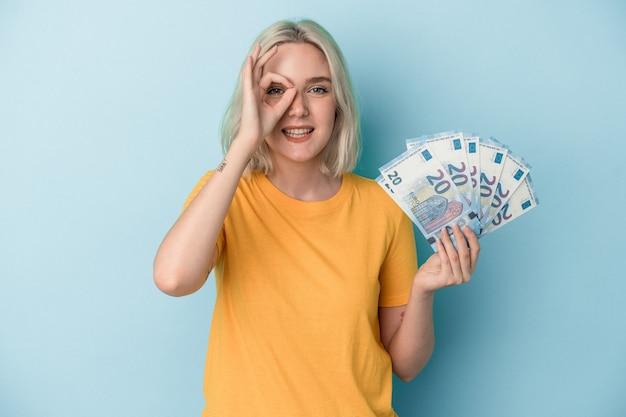 Jeune femme caucasienne tenant des factures isolées sur fond bleu excitée en gardant un geste ok sur les yeux.