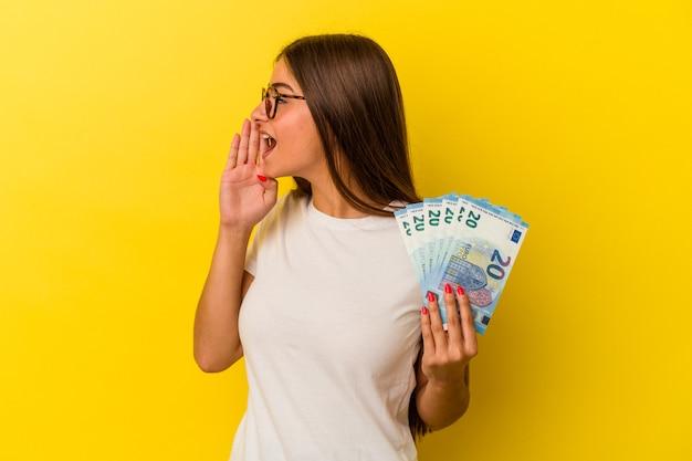 Jeune femme caucasienne tenant des factures isolées sur fond jaune criant et tenant la paume près de la bouche ouverte.
