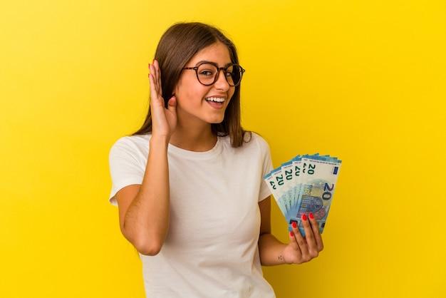Jeune femme caucasienne tenant des factures isolées sur fond jaune essayant d'écouter un potin.