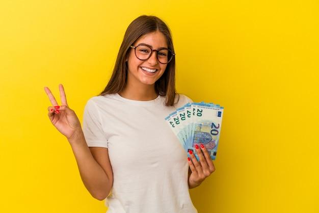 Jeune femme caucasienne tenant des factures isolées sur fond jaune joyeuse et insouciante montrant un symbole de paix avec les doigts.