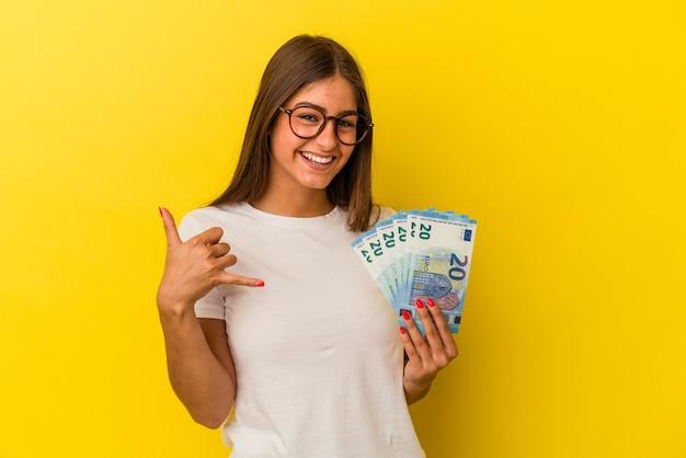 Jeune femme caucasienne tenant des factures isolées sur fond jaune montrant un geste d'appel de téléphone portable avec les doigts.