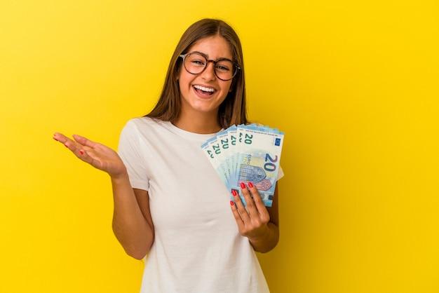 Jeune femme caucasienne tenant des factures isolées sur fond jaune recevant une agréable surprise, excitée et levant les mains.