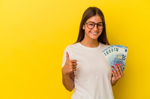 Jeune femme caucasienne tenant des factures isolées sur fond jaune souriant et levant le pouce vers le haut