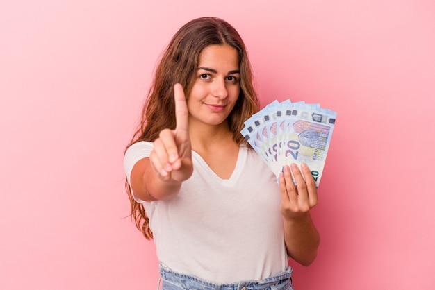 Jeune femme caucasienne tenant des factures isolées sur fond rose montrant le numéro un avec le doigt.
