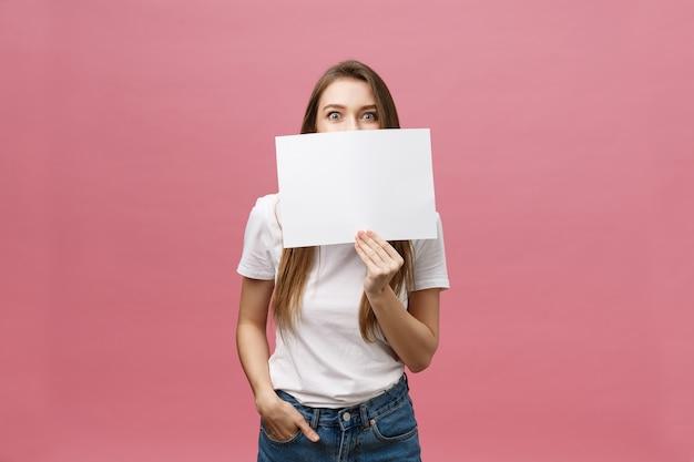 Jeune femme caucasienne tenant une feuille de papier vierge