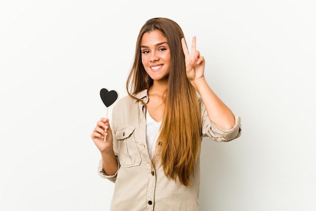 Jeune femme caucasienne tenant une forme de coeur montrant le signe de la victoire et souriant largement.