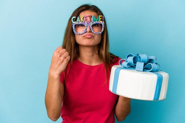 Jeune femme caucasienne tenant un gâteau isolé sur fond bleu montrant le poing à la caméra, expression faciale agressive.