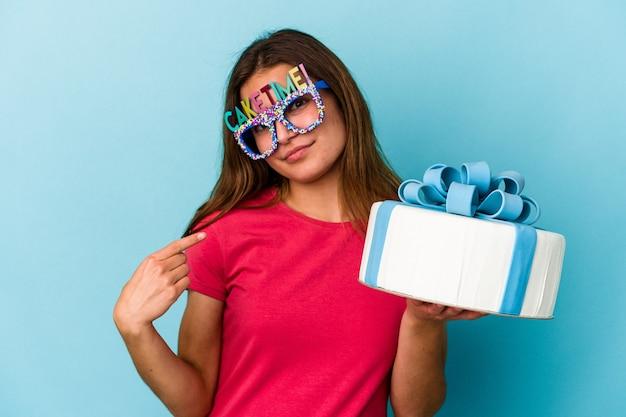 Jeune femme caucasienne tenant un gâteau isolé sur fond bleu pointant du doigt vers vous comme si vous vous invitiez à vous rapprocher.