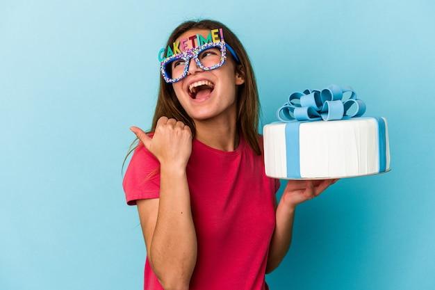 Jeune femme caucasienne tenant un gâteau isolé sur fond bleu points avec le pouce loin, riant et insouciant.