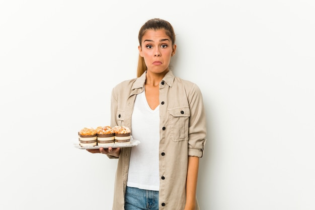 Jeune femme caucasienne tenant des gâteaux sucrés