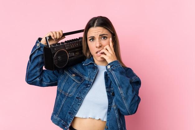 Jeune femme caucasienne tenant un guetto blaster se ronger les ongles, nerveux et très anxieux.