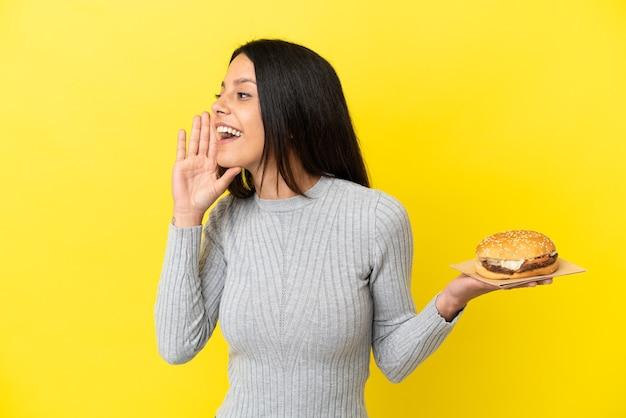 Jeune femme caucasienne tenant un hamburger isolé sur fond jaune criant avec la bouche grande ouverte sur le côté