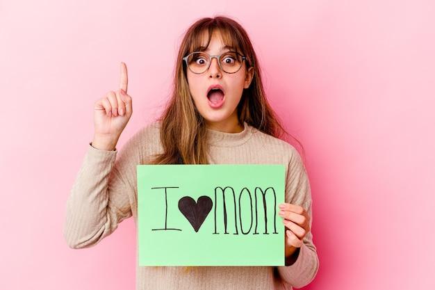 Jeune femme caucasienne tenant un j'aime maman ayant une idée, un concept d'inspiration.