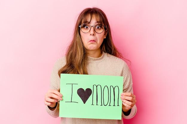 Jeune femme caucasienne tenant un j'aime maman isolée hausse les épaules et les yeux ouverts confus.