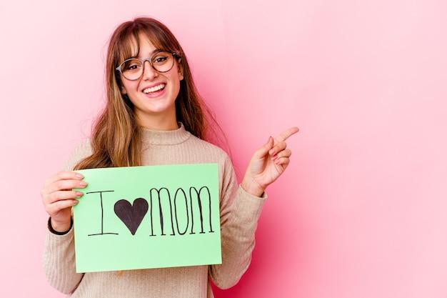 Jeune femme caucasienne tenant un j'aime maman isolée souriant et pointant de côté, montrant quelque chose à l'espace vide.