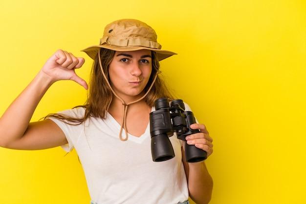 Jeune femme caucasienne tenant des jumelles isolées sur fond jaune montrant un geste d'aversion, les pouces vers le bas. notion de désaccord.
